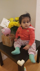 Aadhya sitting by the side of her new piggy bank.
